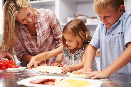 mom son: Mother preparing pizza with kids