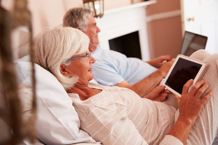 Senior Couple Lying In Bed Using Digital Devices photo