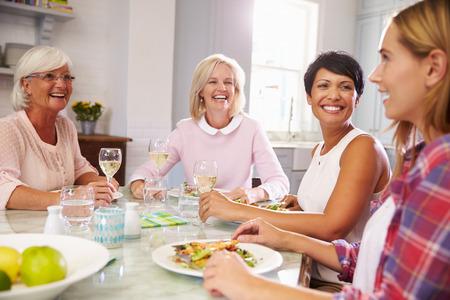 집에서 식사를 즐기는 성숙한 여인 친구의 그룹 스톡 콘텐츠
