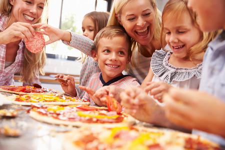 Two women making pizza with kids