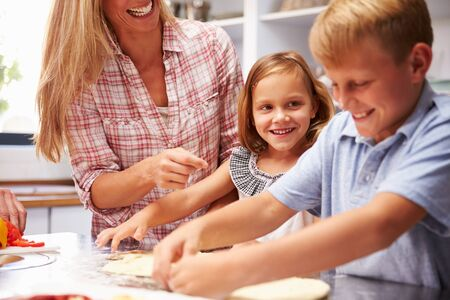 life at home: Mother preparing pizza with kids