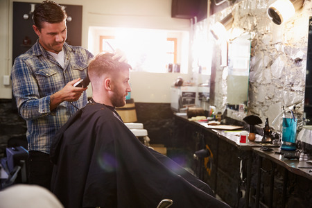 hairdressers: Male Barber Giving Client Haircut In Shop