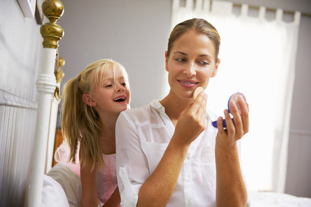 getting together: Daughter Watching Working Mother Put On Make Up