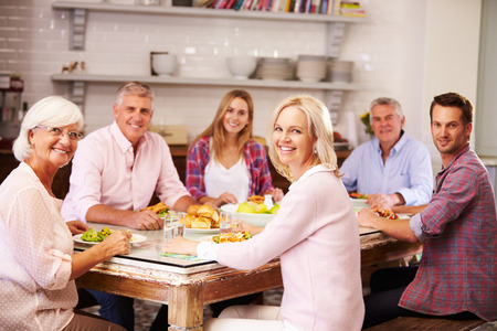 female friends: Portrait Of Friends Enjoying Meal At Home Together