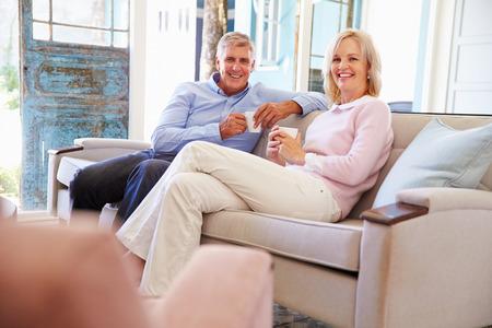 personas sentadas: Pareja madura en el país que se relaja en salón con la bebida caliente