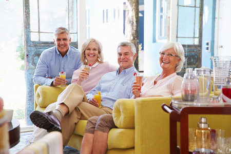 retirement happy man: Group Of Friends At Home Relaxing In Lounge With Cold Drinks