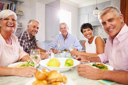 Portret van volwassen Vrienden die van Maaltijd thuis samen Stockfoto