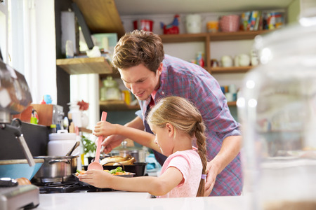 people cooking: Daughter Helping Father To Cook Meal In Kitchen