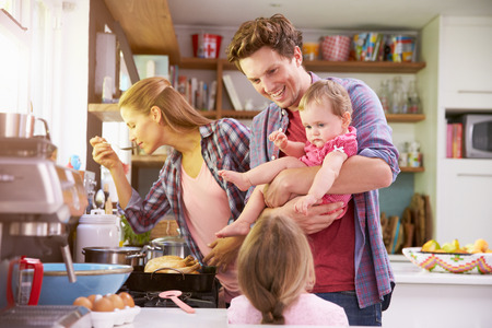 child food: Family Cooking Meal In Kitchen Together
