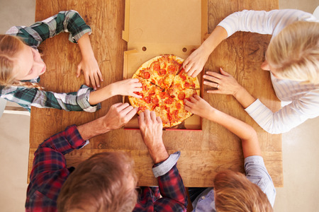 pizzas: Family eating pizza together, overhead view