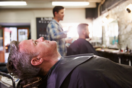 reclining chair: Customer Reclining In Barbers Chair Ready For Shave Stock Photo