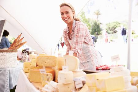 농부 음식 시장에서 신선한 치즈를 판매하는 여자 스톡 콘텐츠