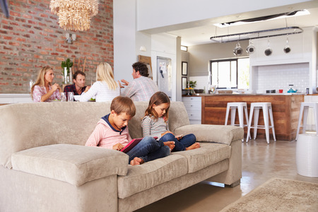 Kids playing with new technology while adults entertain Stock Photo