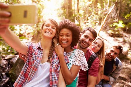 with friends: Grupo de amigos en caminata Tomando selfie En Bosque
