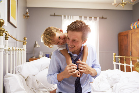 getting together: Son Hugging Father As He Gets Dressed For Work Stock Photo