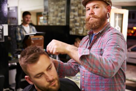 horizontal haircut: Portrait Of Male Barber Giving Client Haircut In Shop