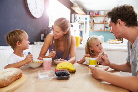 woman eating fruit: Family Eating Breakfast At Kitchen Table Stock Photo