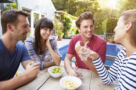 vaso con agua: Grupo de amigos que disfrutan de bebidas al aire libre en el jardín