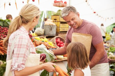market stall: Family Buying Fresh Vegetables At Farmers Market Stall Stock Photo