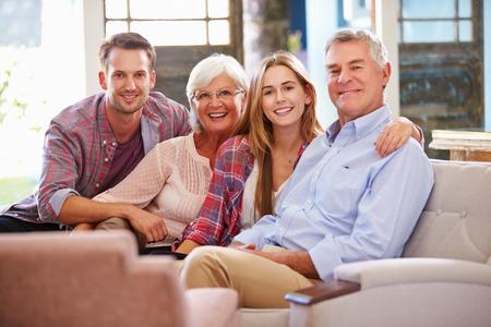 papa y mama: Familia con ni�os adultos relaja en el sof� en el pa�s junto Foto de archivo