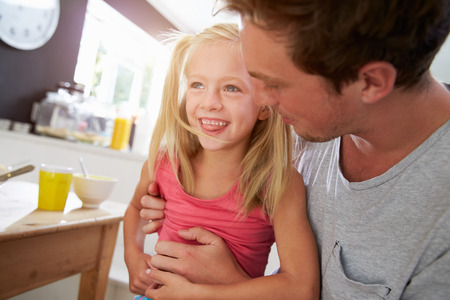 tickling: Father Sitting With Laughing Daughter At Breakfast Table