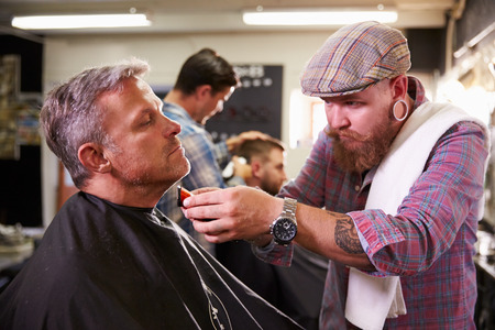 horizontal haircut: Male Barber Giving Client Shave In Shop