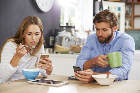 whilst: Young Couple Eating Breakfast Whilst Using Mobile Phones