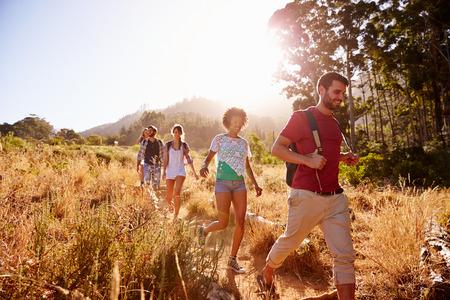 caminando: Grupo de amigos en caminata a través del campo Juntos