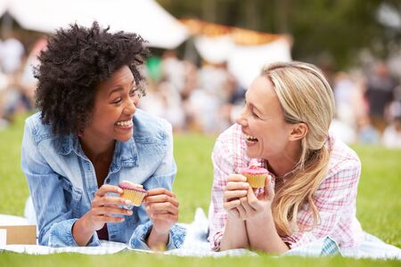 fair woman: Two Female Friends Enjoying Cupcakes At Outdoor Summer Event