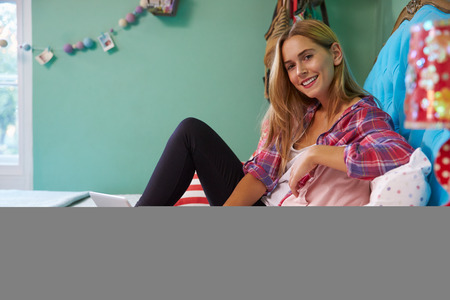 relaxing at home: Woman Sitting On Bed At Home Using Digital Laptop Computer Stock Photo