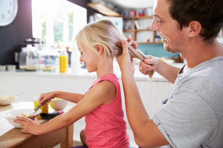 hair styling: Father Styling Daughters Hair At Breakfast Table Stock Photo