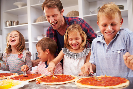 busy life: Father making pizza with his kids Stock Photo