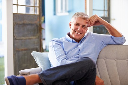 relaxing at home: Portrait Of Smiling Mature Man Sitting On Sofa At Home