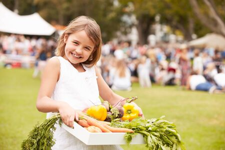 7 years old: Girl With Fresh Produce Bought At Outdoor Farmers Market Stock Photo