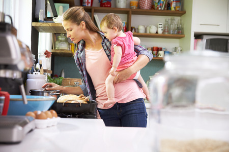 niños cocinando: Madre Cocinar la comida mientras Holding Hija En Cocina