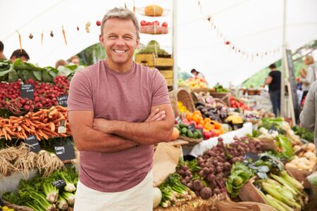 market stall: Male Stall Holder At Farmers Fresh Food Market Stock Photo