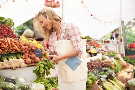 농민 시장 마구간에서 여성 고객 쇼핑