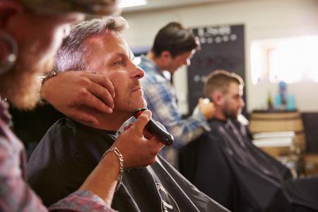 ショップでクライアントのひげそりを与える男性の床屋
