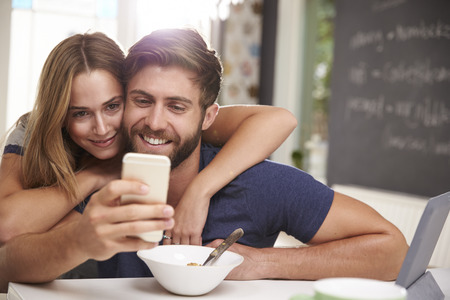 beard woman: Couple Eating Breakfast Using Digital Tablet And Phone