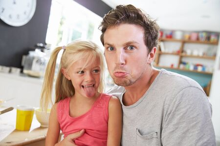 children face: Father And Daughter Making Funny Faces At Breakfast Table Stock Photo