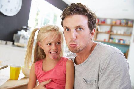 lachendes gesicht: Vater und Tochter, die lustige Gesichter am Frühstückstisch