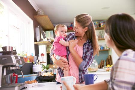 amigos abrazandose: Madre Con Hija joven que habla con el amigo en la cocina