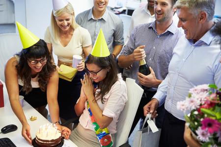 middle adult: Celebrating a colleagues birthday in the office Stock Photo