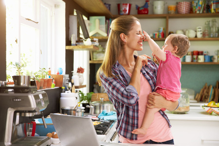 Mother With Young Daughter Using Laptop In Kitchen photo