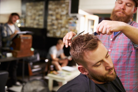 shop owner: Male Barber Giving Client Haircut In Shop