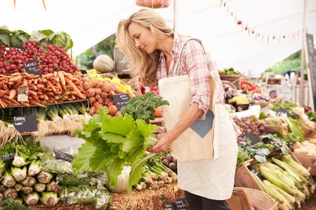 農民市場の屋台で買い物する女性客 写真素材