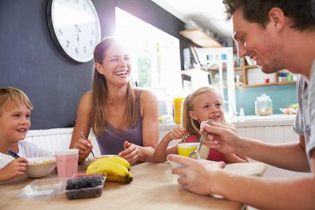 家族: 台所のテーブルで朝食を食べて家族