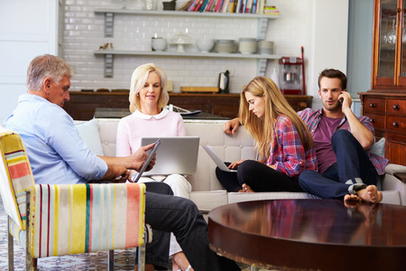 family at home: Parents With Adult Offspring Using Digital Devices At Home