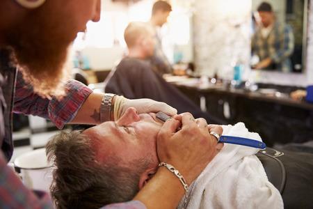 barbero: Peluquer�a afeitar Cliente Con Cut Throat Razor Foto de archivo