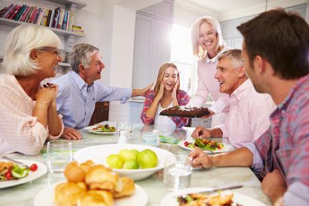 fiesta familiar: Madre Sirve torta de cumplea�os a la hija adulta Al comida familiar
